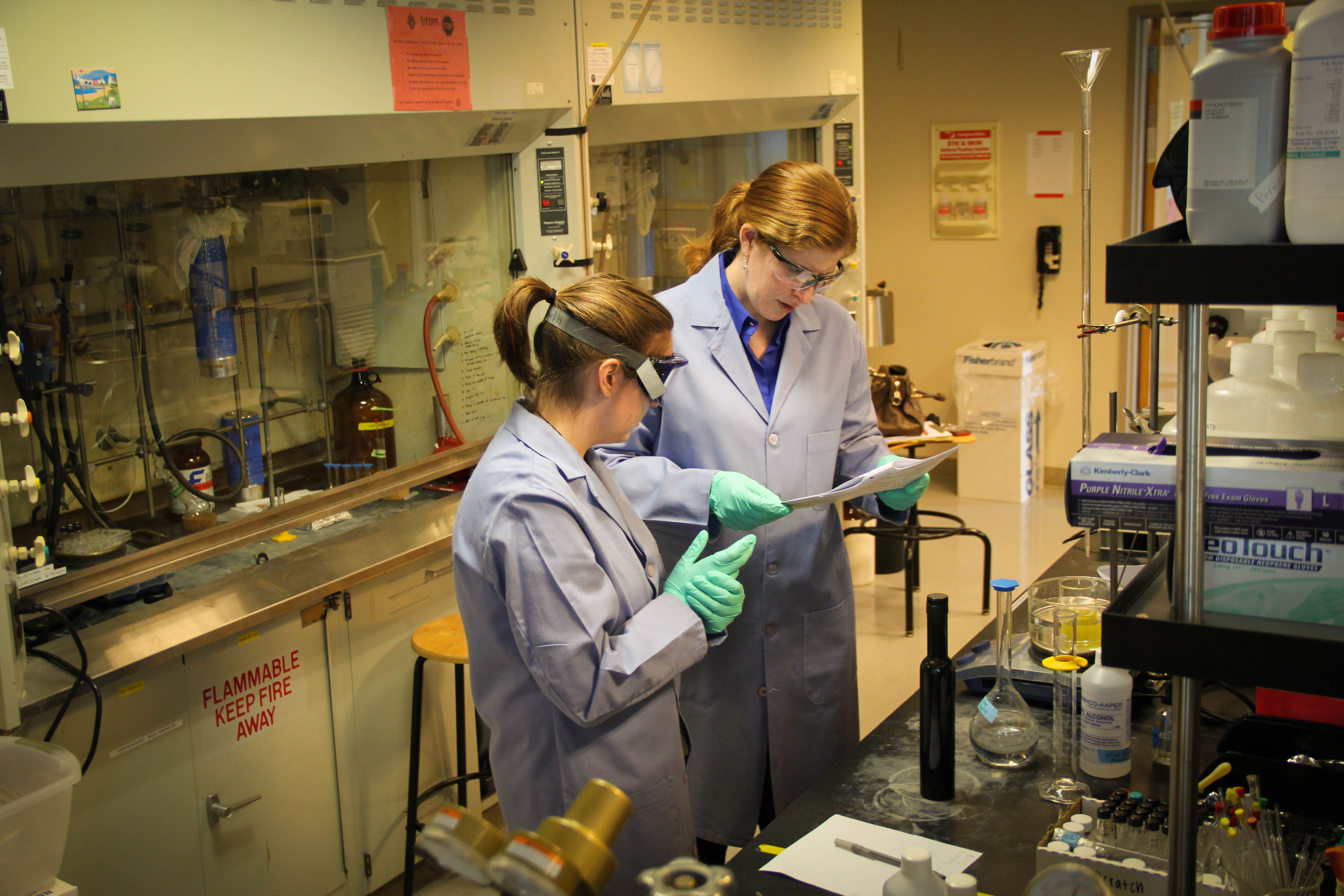 two people in lab coats and goggles looking at a clipboard