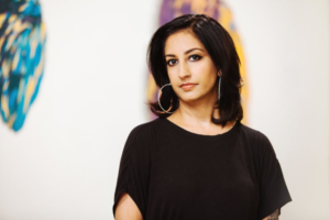 A photo of a South Asian woman with short black hair and wearing a black blouse looking at the camera.