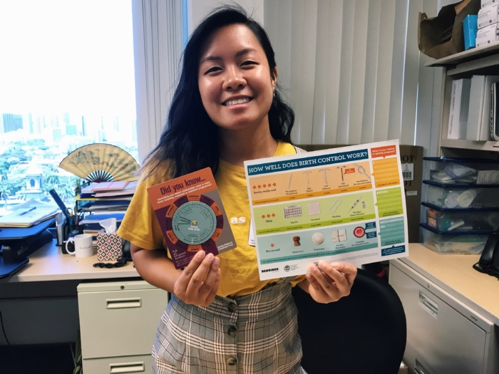 A young Hawaiian woman in a yellow t-shirt and plaid coveralls holding up informational cards about birth control.