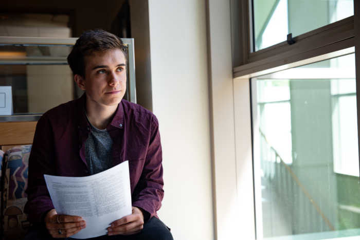 A young man with short brown hair and wearing a red shirt sitting indoors with a paper in his hands and looking out a window.