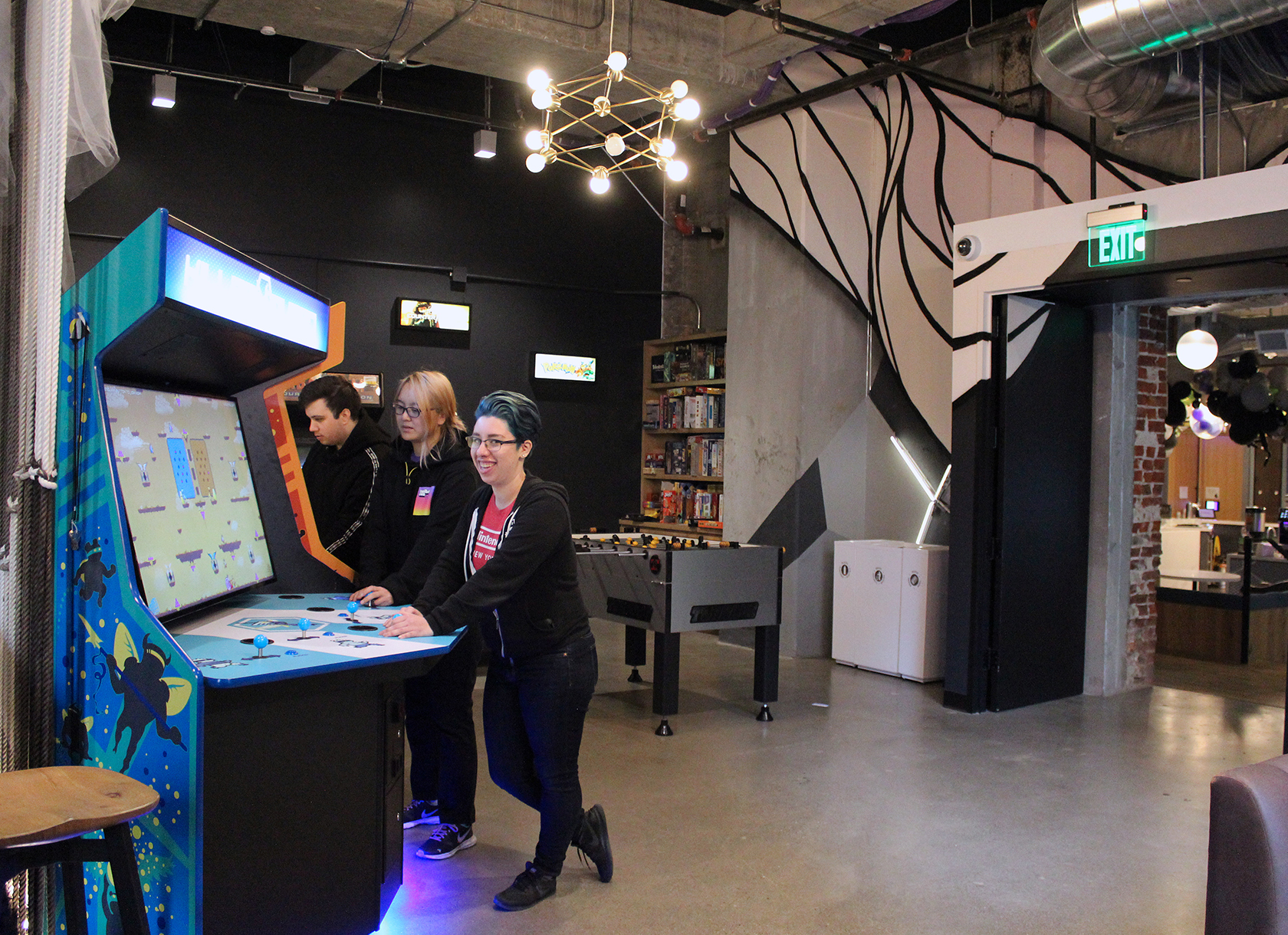 Three people playing arcade games in a game room.