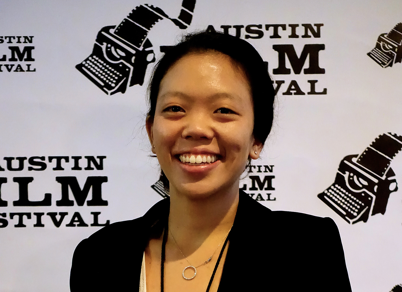 A headshot of a smiling Asian woman wearing a black blazer at a film festival.