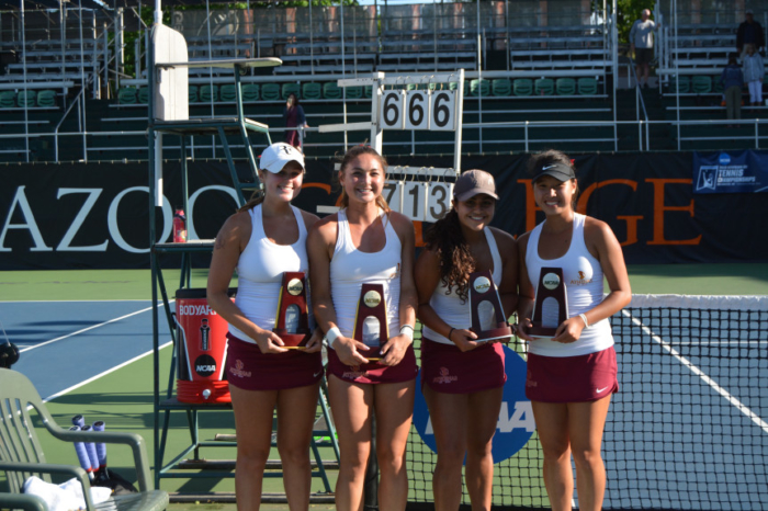 Four young women in sports uniforms posing with awards on a tennis court.