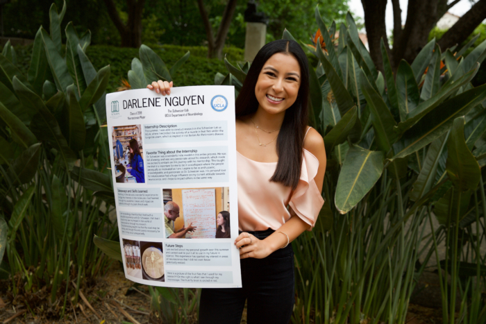 A young Asian woman in formal clothing smiling and holding up a poster outside.