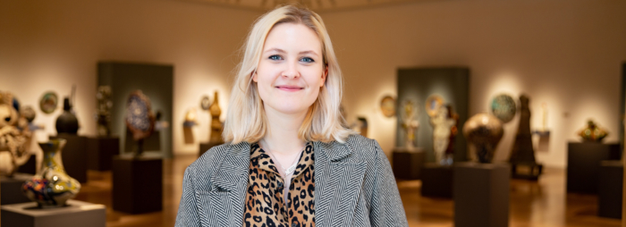 A young white woman with blond hair wearing a blazer and leopard print shirt smiling in an art gallery.