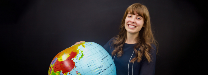 A young woman with long brown hair smiling and wearing a professional blue sweater holding an inflatable globe.