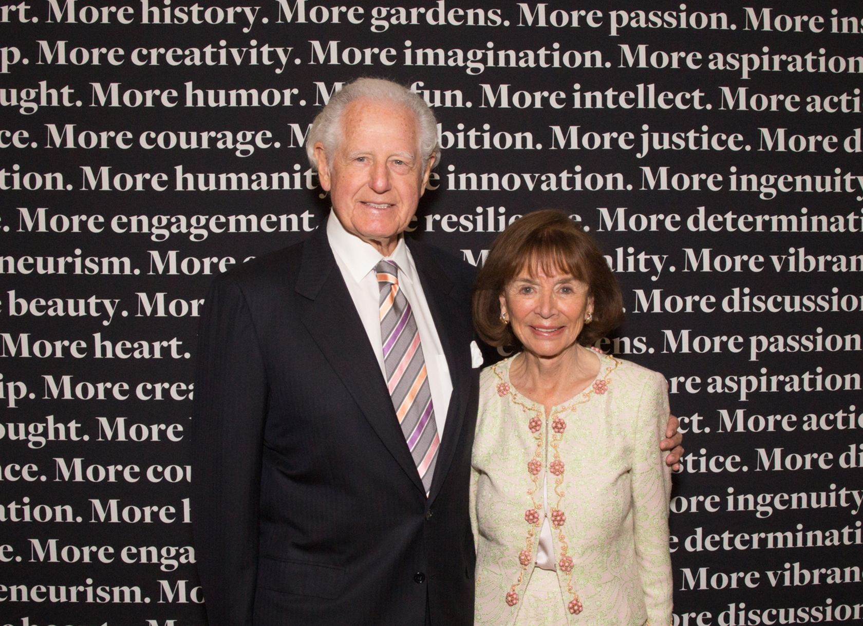 A white man and woman posing together in professional dress.
