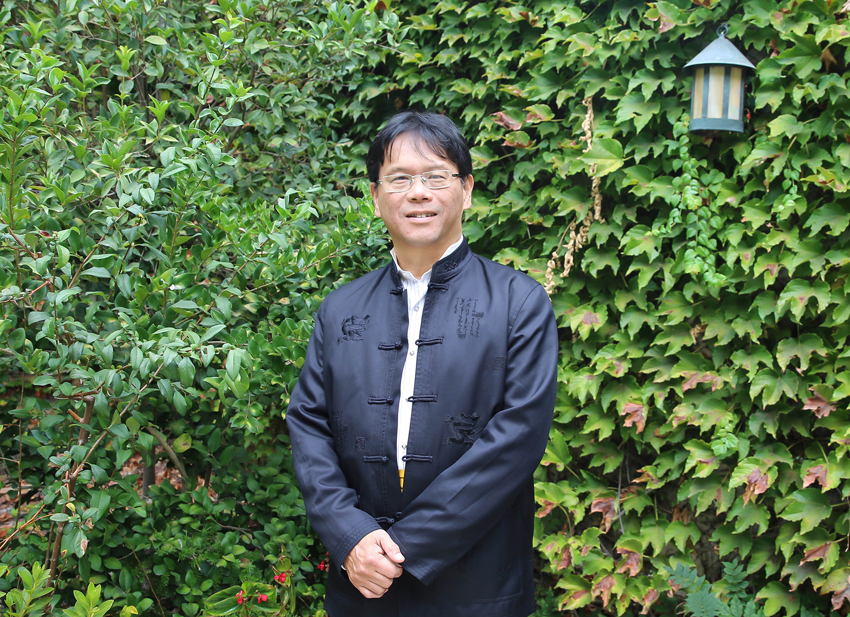 An Asian man with black hair wearing glasses and black traditional clothing.