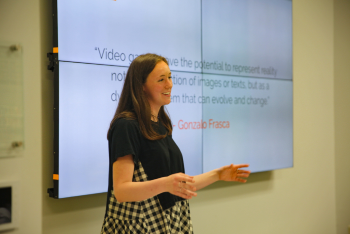A young white woman in formal clothing giving a presentation at the front of a room.