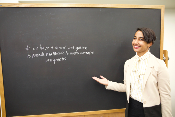 A young South Asian woman in formal clothing standing at a blackboard.