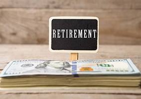 "Dollar bills, blackboard with text ""Retirement"" on wooden background"