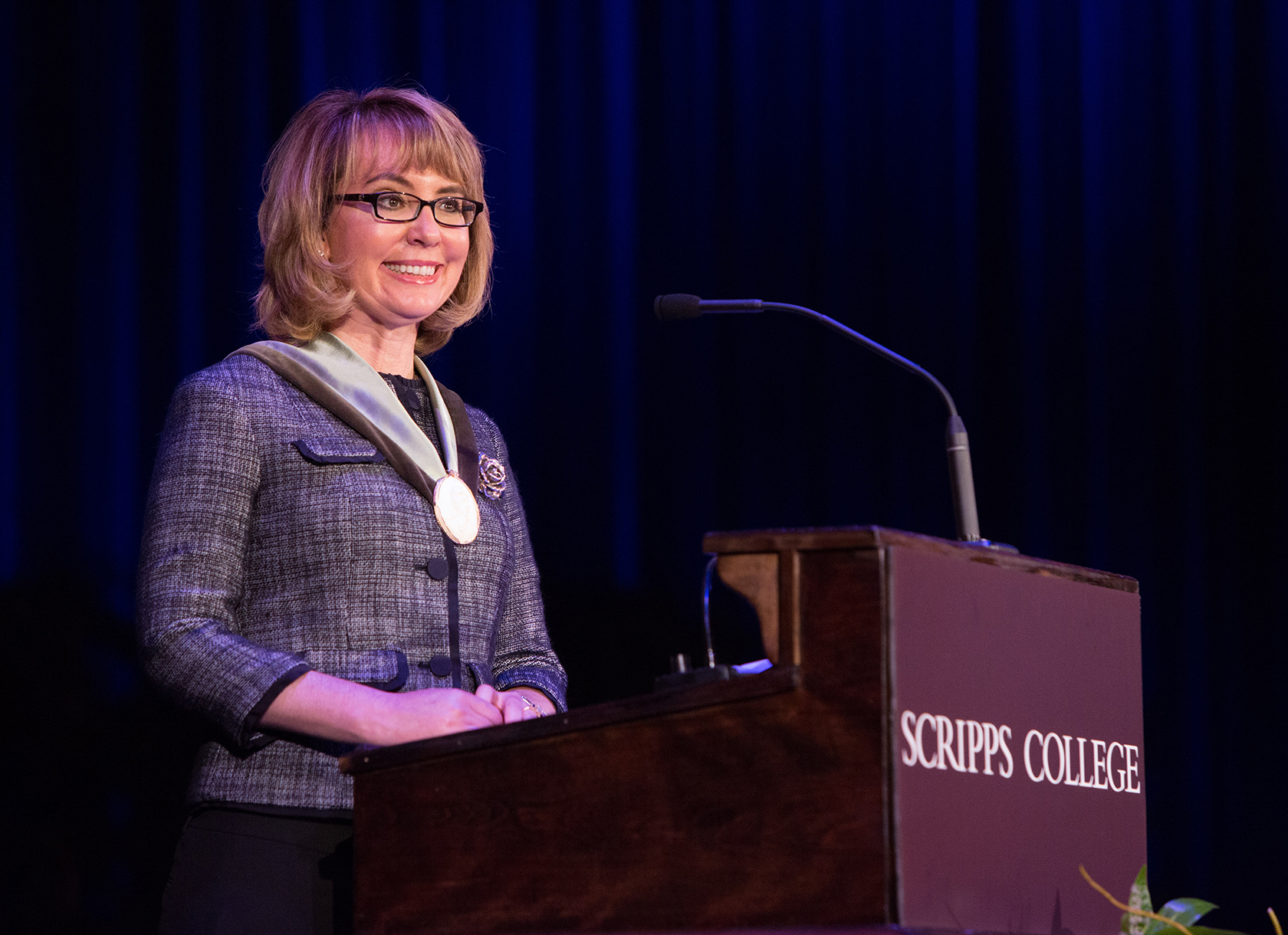 A white woman with short blonde hair and glasses stands behind a Scripps College podium
