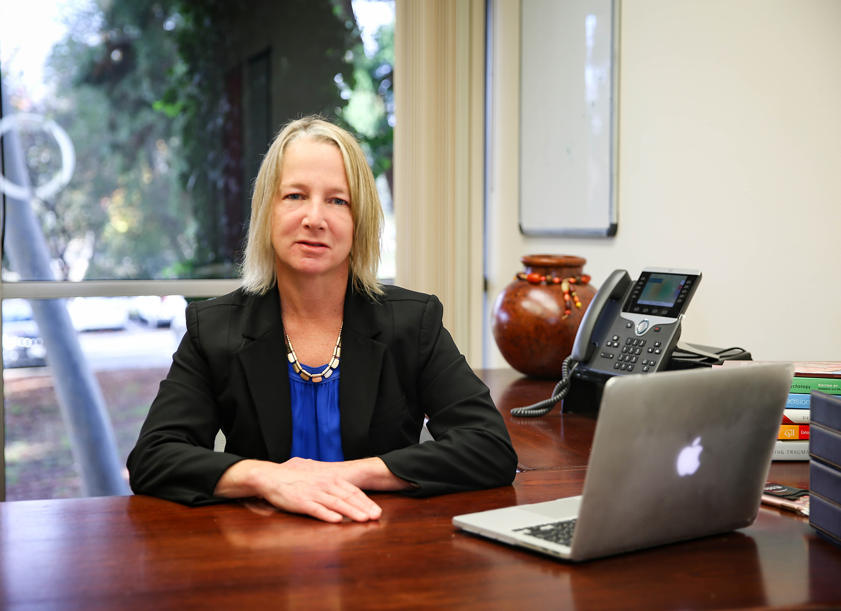 Blonde white woman in blazer sits behind desk with laptop