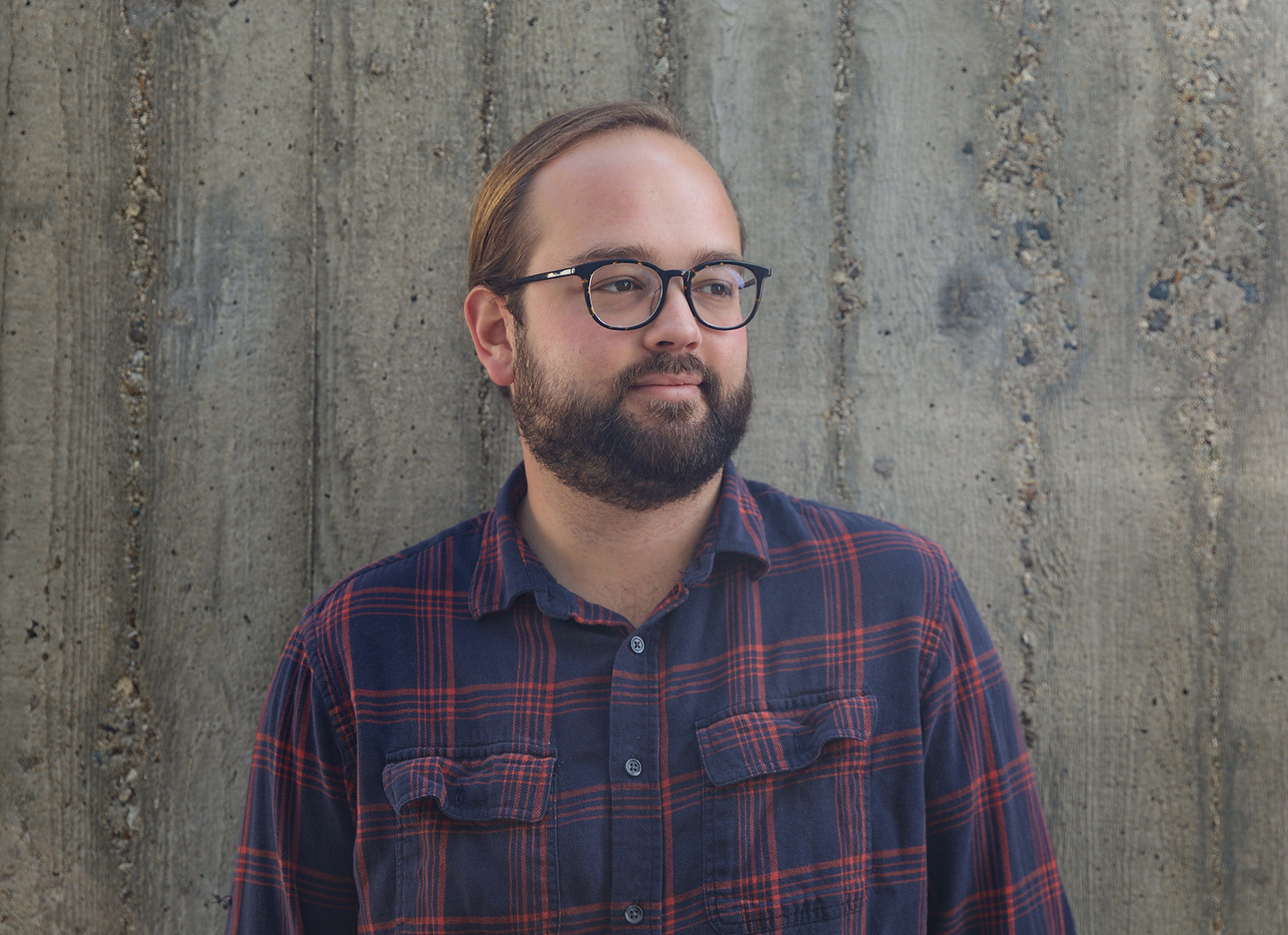 Bearded white man wearing plaid shirt and glasses looks to the right