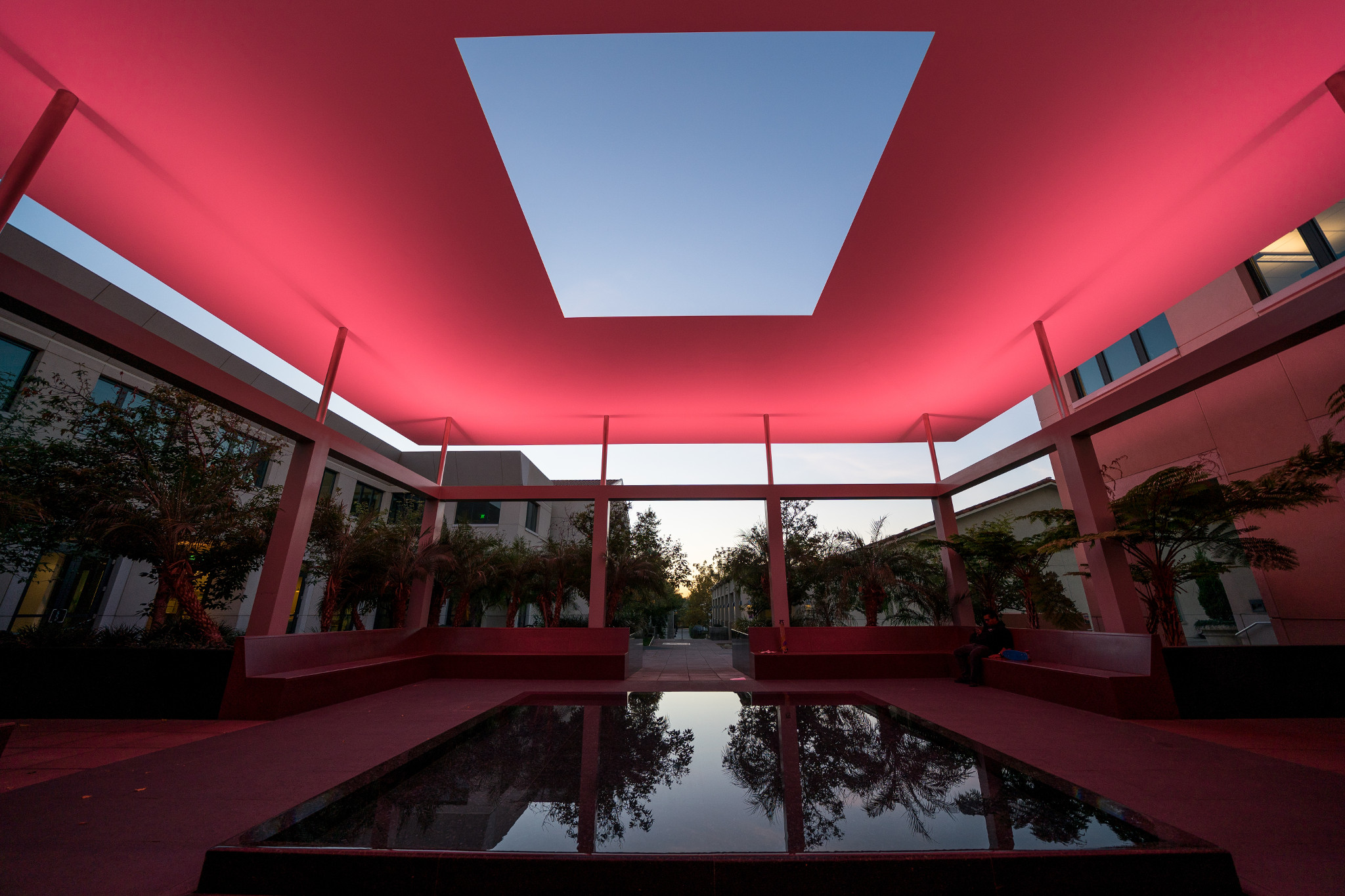 An art exhibition featuring a reflective pool and glowing red light.