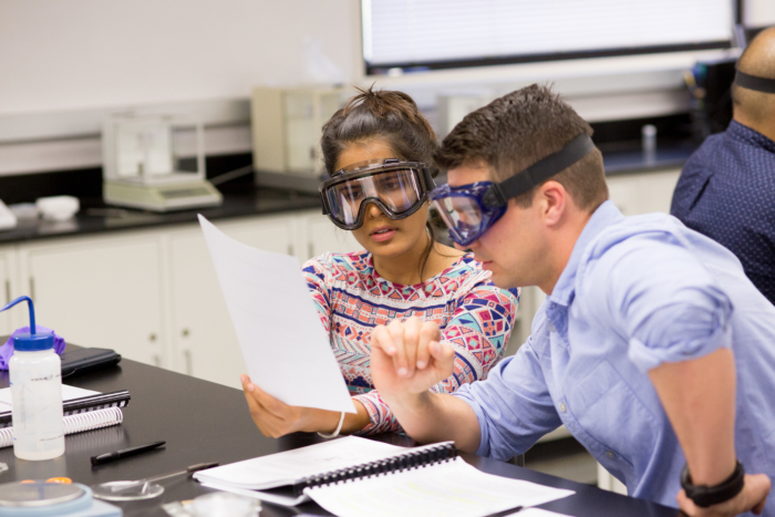 Two people wearing lab goggles and looking at papers while working at a lab table.
