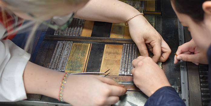 A close-up of hands crafting a book.