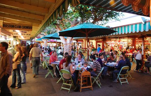 A crowded Original Farmers Market with people eating at tables, standing around, and shopping.