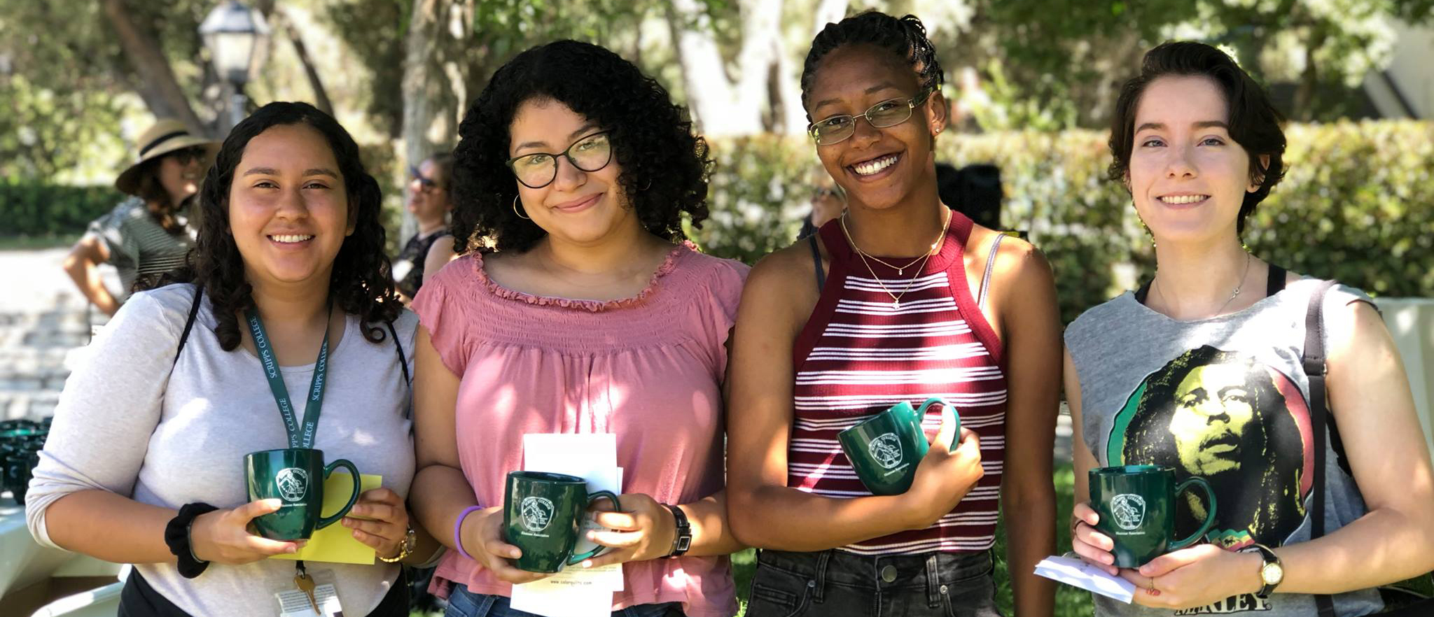 Four Scripps students posing in Elm Tree Lawn with green Scripps mugs.