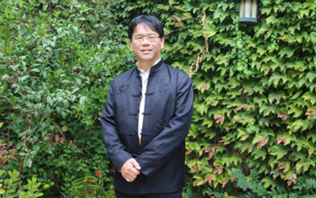 Professor Hao Huang strikes a pose among the leaves