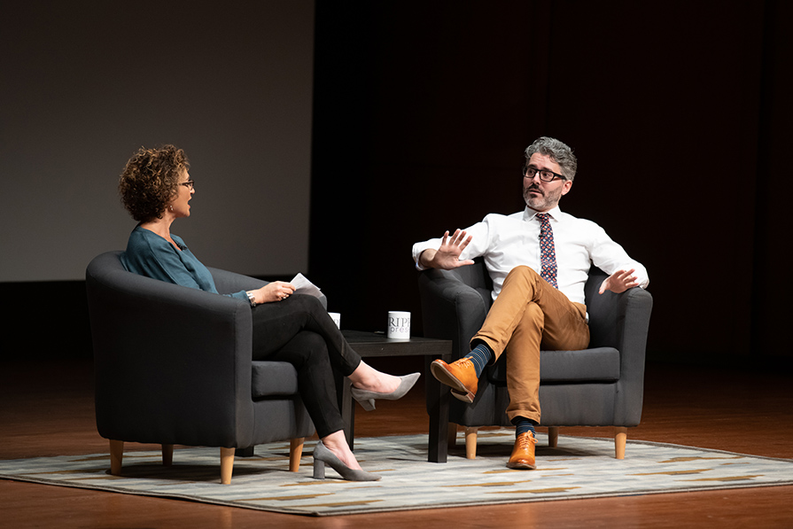 A white man with gray hair and glasses sitting on stage across from a woman with glasses and short brown curly hair.