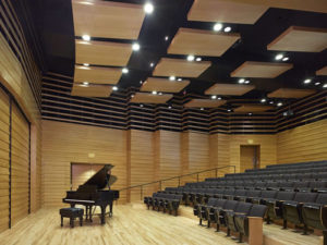 A music auditorium with a grand piano and rows of seats.