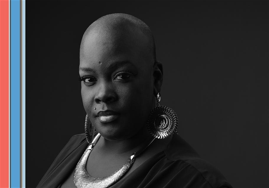A black and white photo of a bald black woman wearing earrings and a blazer looking at the camera.