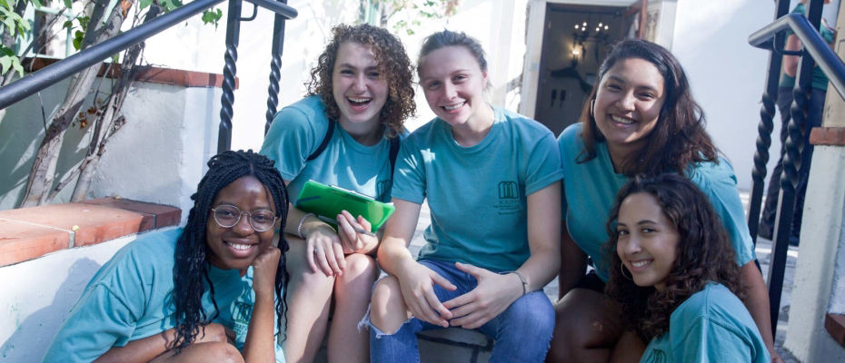five scripps students smiling and sitting on staircase