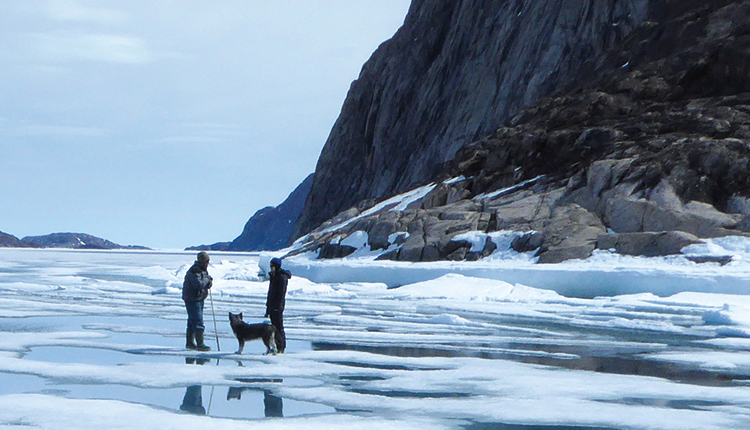 Two people and a dog standing in an icy landscape