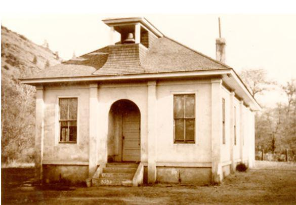 A black and white image of a small schoolhouse with a bell.
