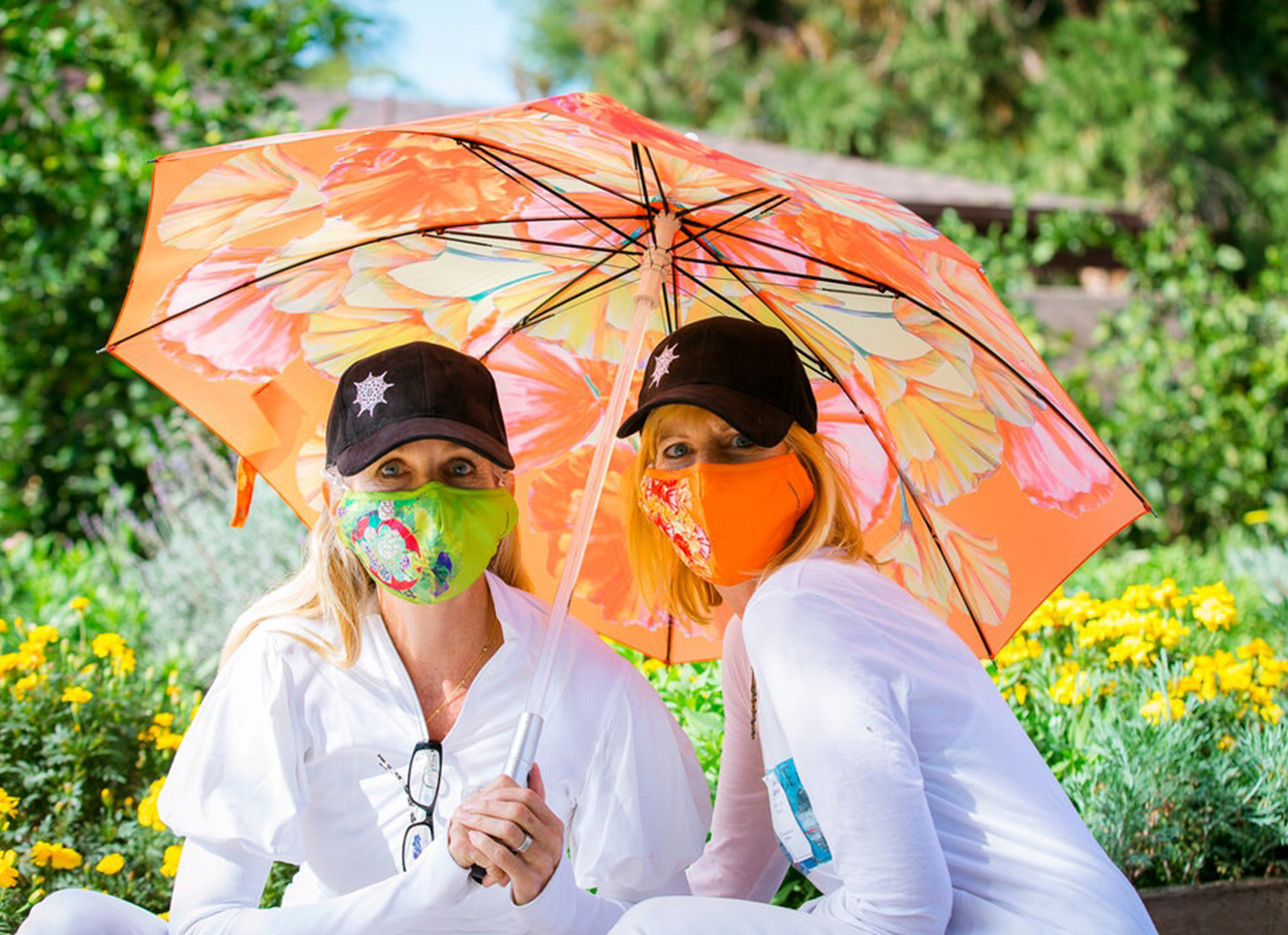 Two White women dressed in white wear masks and hold an orange umbrella