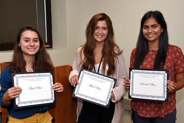 Three young woman each holding a certificate for first, second, or third place.