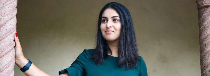 A young South Asian woman with black hair and a green shirt smiling and looking to the left.
