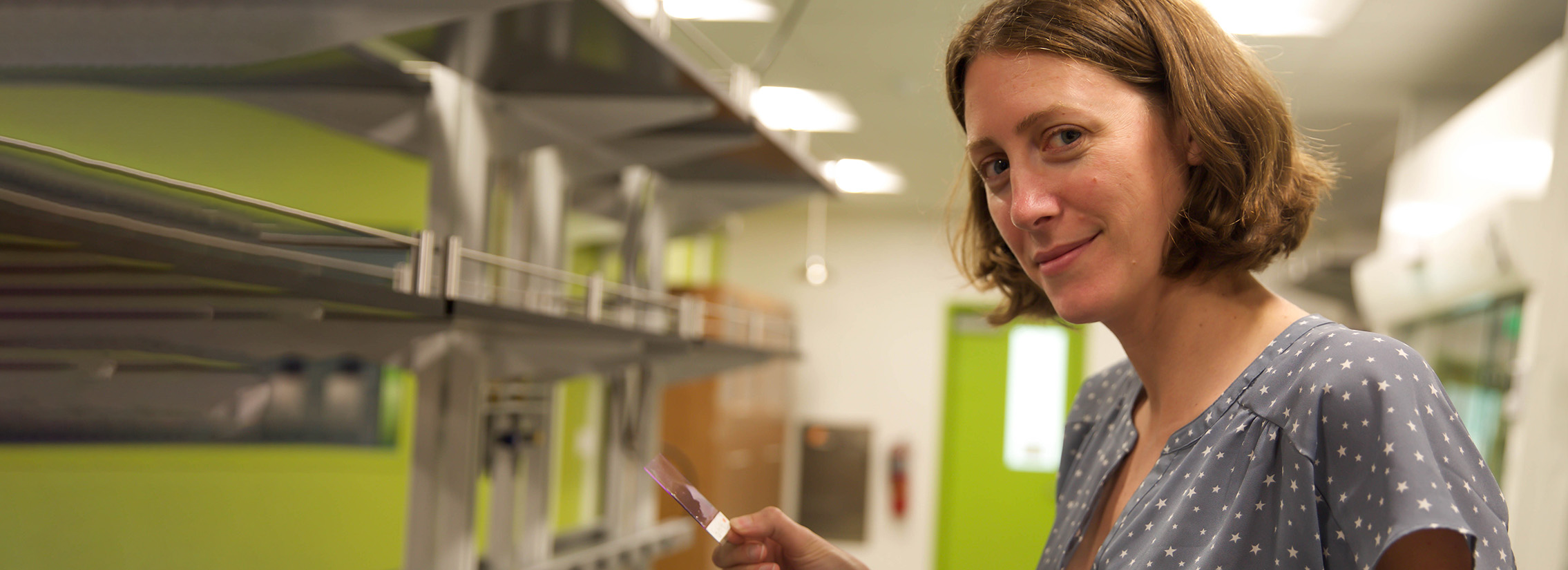 A white woman with short light brown hair holding a microscope slide in a science lab.