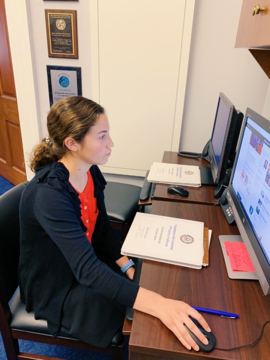 A young white woman with brown hair and wearing professional clothing working at a desktop computer.