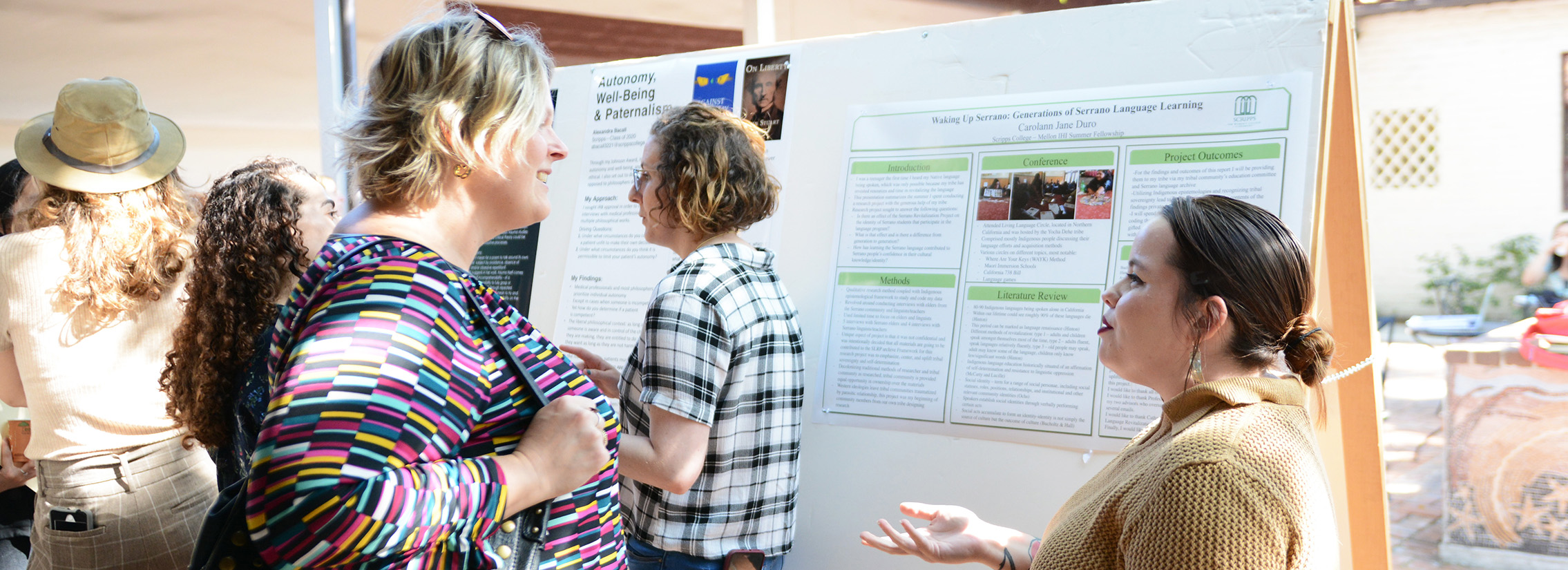 A woman with brown hair in a ponytail talking to a smiling blond woman outside in front of a research poster.