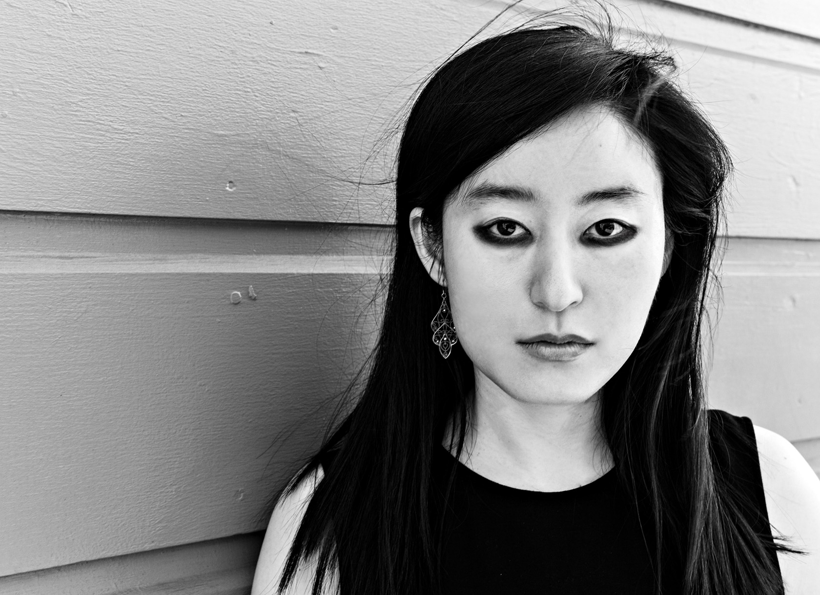 A black and white headshot of a young Asian woman with long black hair and black eyeliner.