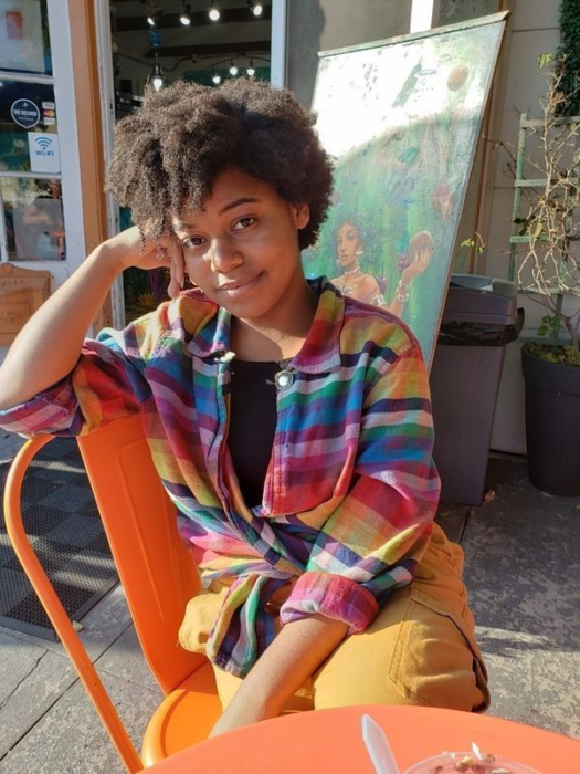 A young woman wearing a rainbow striped shirt and orange pants sitting at a table outside with her elbow rested on her chair and her head rested on her hand.