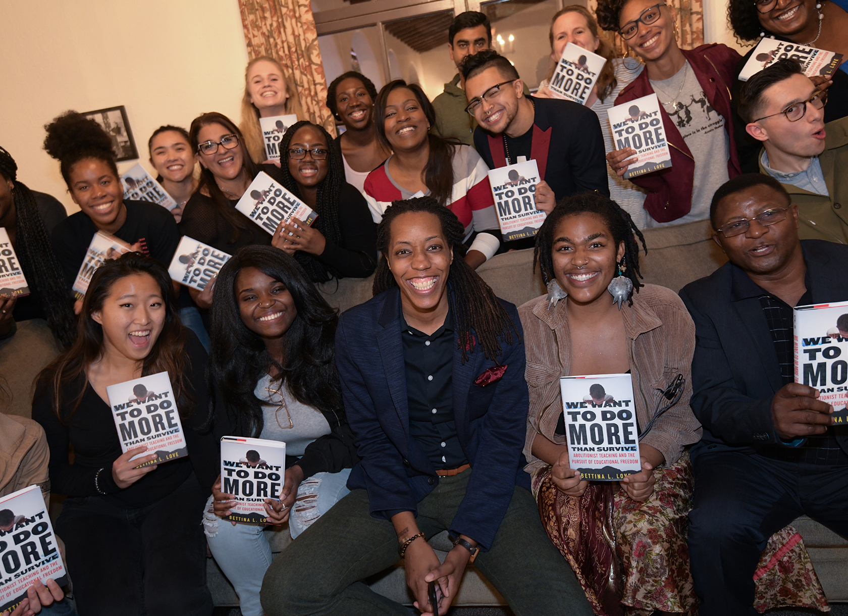 A group of students each holding a book posing with a black woman.