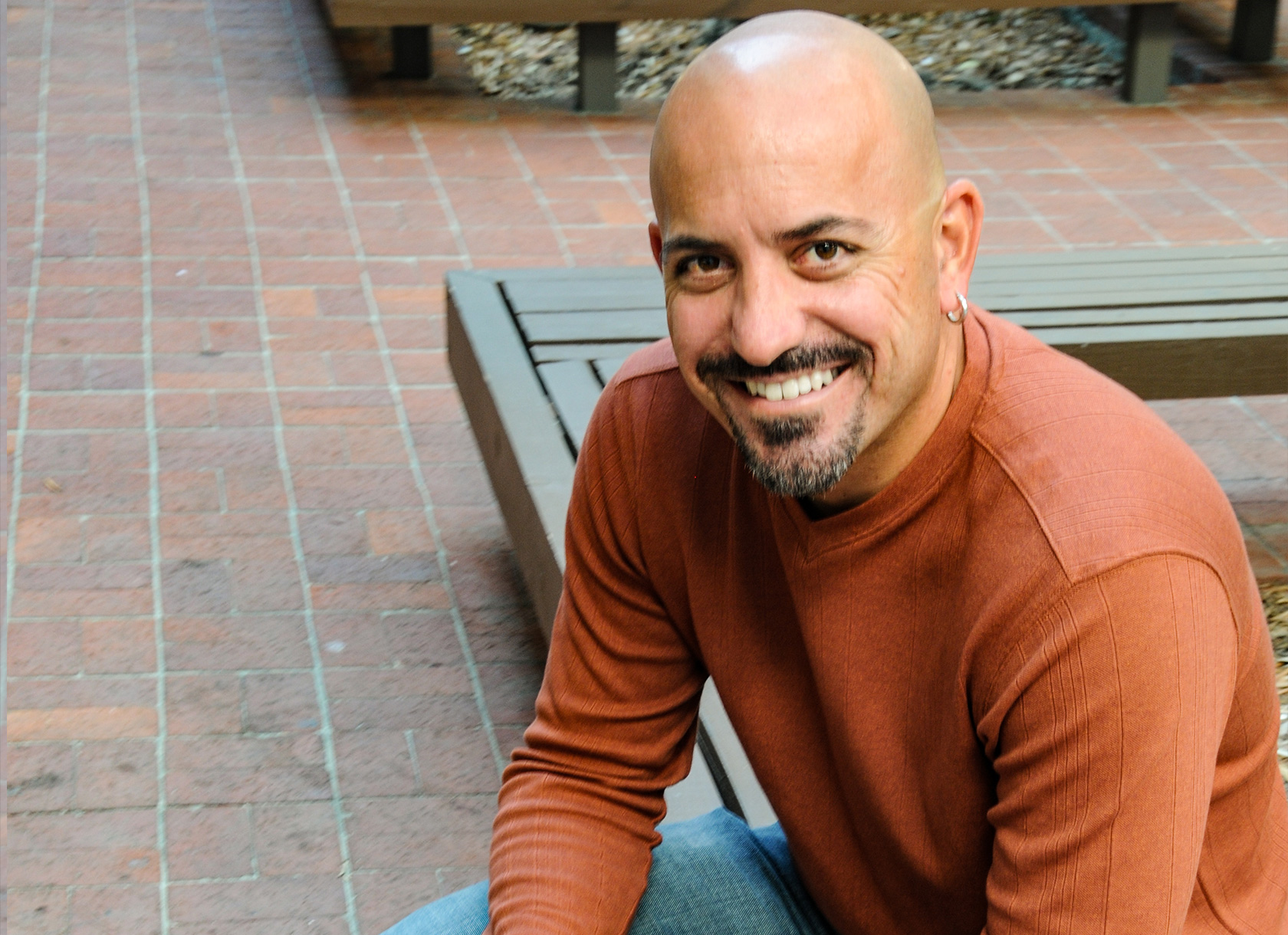 A bald, bearded man in an orange sweater and jeans smiles at the camera from a seated position