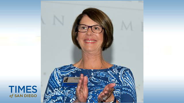 A woman with short brown hair. glasses, and a nametag wearing glasses and looking up while clapping in a photo from the Times of San Diego.