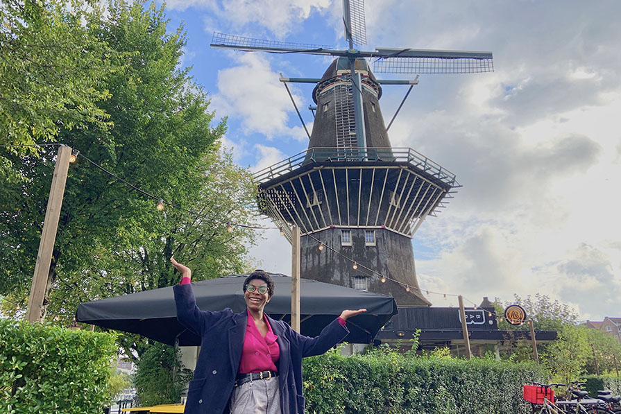 student abroad in the Netherlands standing in front of a windmill