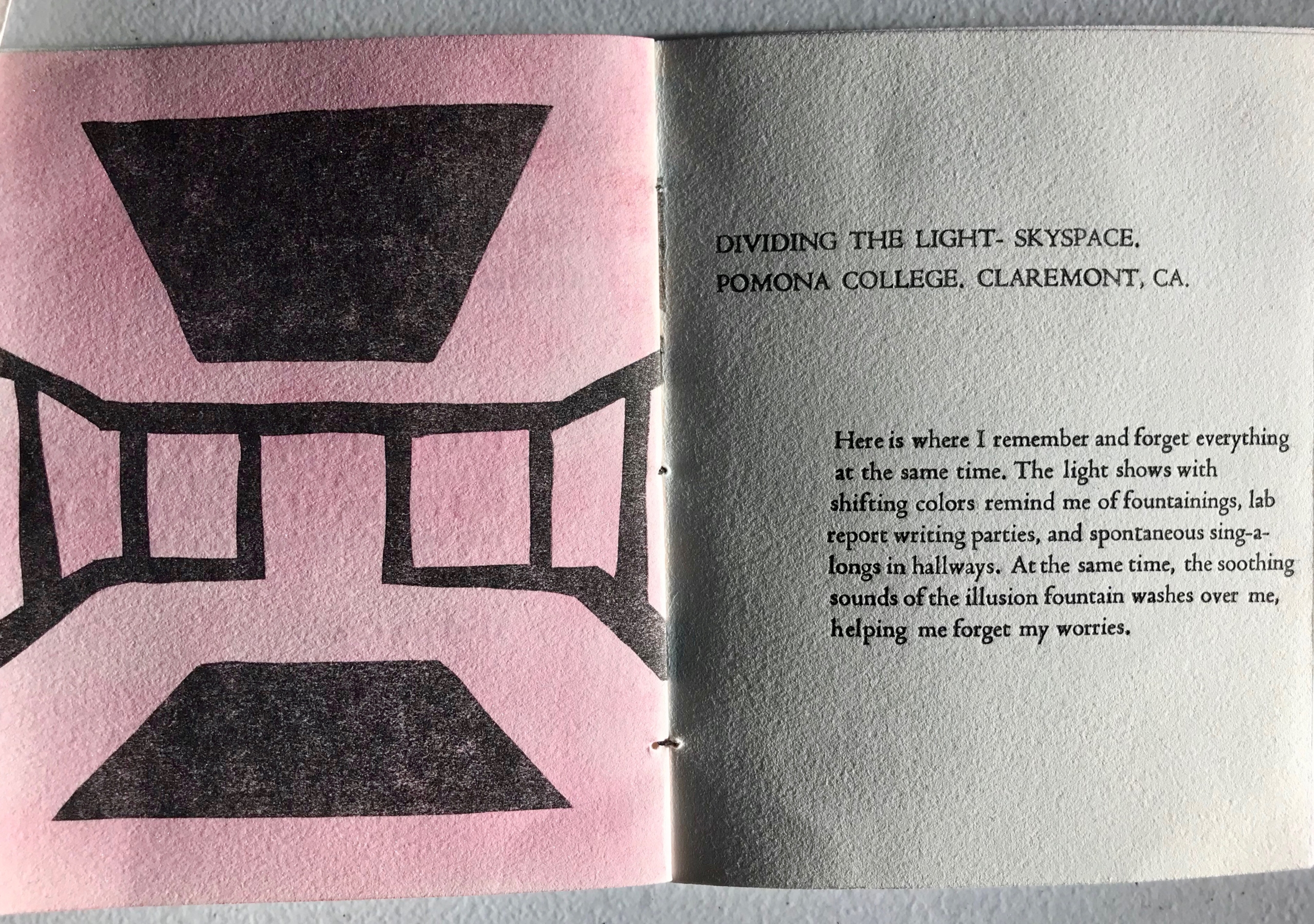 An open handcrafted book with a pink and black visual covering one page.