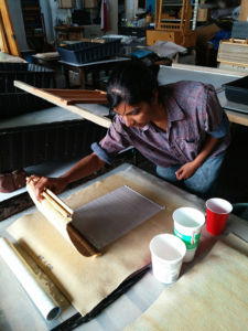 A brown woman with black hair making paper.